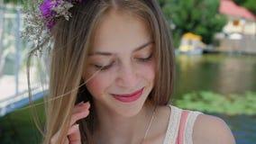 La ragazza felice con i wildflowers in mani guarda intorno, sorridendo nel giorno ventoso soleggiato stock footage