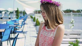 La ragazza felice con i wildflowers in mani guarda intorno, sorridendo nel giorno ventoso soleggiato archivi video