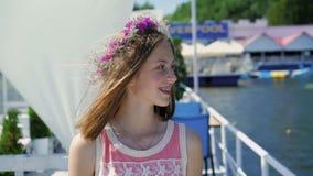 La ragazza felice con i wildflowers in mani guarda intorno, sorridendo nel giorno ventoso soleggiato video d archivio