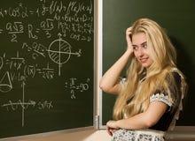 La ragazza felice del banco su per la matematica classifica l'individuazione della soluzione Fotografia Stock