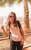 La ragazza felice del viaggiatore è vicino alla finestra dell'aeroporto Fotografie Stock Libere da Diritti