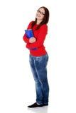La ragazza felice dell'allievo è dispositivi di piegatura e sorridere della holding. Immagine Stock Libera da Diritti