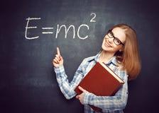 La ragazza felice dello studente con il libro ed i vetri ha scritto sul blackbo Immagini Stock Libere da Diritti