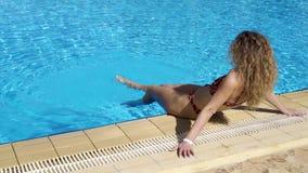 La ragazza felice dentro si siede sull'orlo di uno stagno all'aperto Muove il suo piede nell'acqua Un resto reale dallo stagno Lo video d archivio
