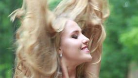 La ragazza felice dissolve i capelli lunghi sulla natura dell'estate video d archivio