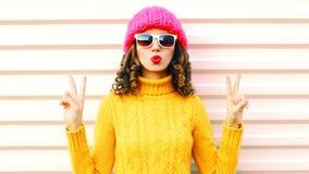 La ragazza felice divertente che soffia le labbra rosse fa il bacio dell'aria che porta il cappello giallo tricottato variopinto  immagine stock