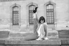 La ragazza felice fa l'esercizio d'allungamento spaccato della gamba sul recinto di pietra Immagine Stock Libera da Diritti