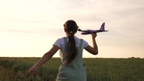 La ragazza felice funziona con un aereo del giocattolo su un giacimento di grano i bambini giocano l'aeroplano del giocattolo sog video d archivio