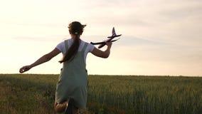 La ragazza felice funziona con un aeroplano del giocattolo su un giacimento di fiore i bambini giocano l'aeroplano del giocattolo stock footage