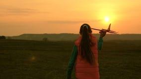 La ragazza felice funziona con un aeroplano del giocattolo sui precedenti di un tramonto sopra il campo Il concetto di una famigl archivi video