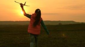 La ragazza felice funziona con un aeroplano del giocattolo sui precedenti di un tramonto sopra il campo Il concetto di una famigl video d archivio