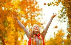 La ragazza felice getta sulle foglie di autunno in parco per la passeggiata all'aperto Fotografia Stock