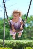 La ragazza felice ride mentre oscilla alla sosta Immagini Stock