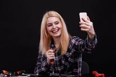 La ragazza felice rompe gli smartphones con uno strumento e fa il selfie su un telefono cellulare Su un fondo nero fotografia stock