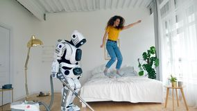 La ragazza felice salta su un letto mentre un robot pulisce il pavimento Robot, cyborg e concetto umano stock footage