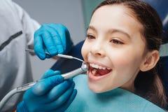 La ragazza felice si siede nella sedia del dentista Tiene la bocca aperta Trapano di uso del dentista e un altro strumento dentar fotografie stock libere da diritti