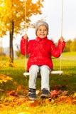 La ragazza felice si siede sulle oscillazioni e sorride allegramente immagini stock