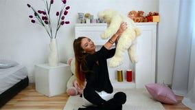 La ragazza felice si siede in una stanza luminosa che sorride e che tiene l'orsacchiotto archivi video