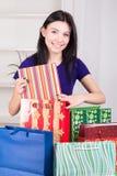 La ragazza felice sorridente prepara i regali delle borse per il Natale fotografia stock libera da diritti