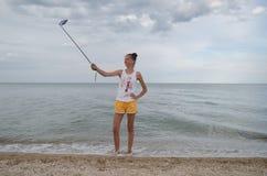La ragazza felice spara il selfie su uno Smart Phone in un viaggio dal mare Immagine Stock