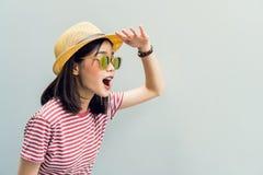 La ragazza felice sta aspettando con impazienza di trovare qualcosa Indossi gli occhiali da sole con una riflessione del sole leg fotografia stock