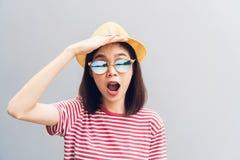 La ragazza felice sta aspettando con impazienza di trovare qualcosa Indossi gli occhiali da sole con una riflessione della spiagg fotografia stock