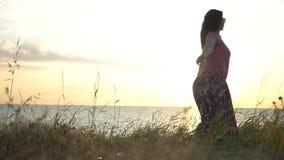 La ragazza felice sta ballando sulla spiaggia sui precedenti del tramonto HD, 1920x1080 Movimento lento video d archivio