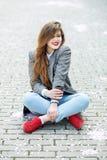 La ragazza felice sta bevendo il caffè caldo e sorridere Si siede sul pavimento Concetto dello stile di vita, urbano, svago, stud immagini stock libere da diritti