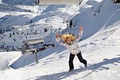 La ragazza felice sta sul pendio dello sci delle montagne Immagine Stock Libera da Diritti