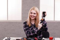 La ragazza felice taglia un coltello della costruzione con uno schermo rotto di uno smartphone e ride allegramente all'interno immagine stock