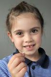 La ragazza felice tiene i suoi primi denti di latte di caduta Fotografie Stock Libere da Diritti