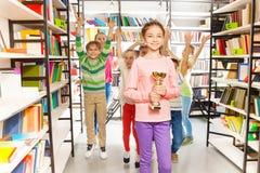 La ragazza felice tiene la tazza dorata, bambini che saltano dietro Fotografia Stock Libera da Diritti