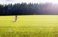 La ragazza felice in una gonna lunga funziona sul campo Immagini Stock