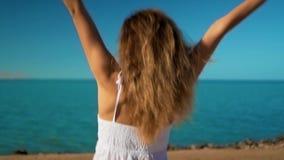 La ragazza felice in vestito bianco funziona al mare e si rallegra archivi video
