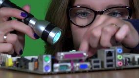 La ragazza femminile del tecnico con i vetri ispeziona le componenti di computer con luce istantanea stock footage