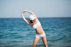 La ragazza femminile esile con la bella figura sta facendo allungando l'esercizio sulla spiaggia, sul funzionamento di mattina, s Fotografia Stock