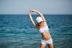 La ragazza femminile esile con la bella figura sta facendo allungando l'esercizio sulla spiaggia, sul funzionamento di mattina, s Fotografie Stock