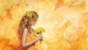 La ragazza fiorisce il mazzo, giovane modello di moda Smelling Yellow Dandelion Immagini Stock
