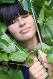 La ragazza in fogliame Fotografie Stock Libere da Diritti