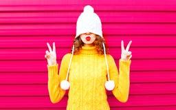 La ragazza fresca che soffia le labbra rosse fa il bacio dell'aria che porta il cappello tricottato variopinto, maglione giallo fotografia stock libera da diritti