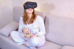 La ragazza fresca guarda il video in vetri di VR, sedentesi sullo strato nel brigh Immagini Stock Libere da Diritti
