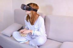 La ragazza fresca guarda il video in vetri di VR, sedentesi sullo strato nel brigh Immagine Stock
