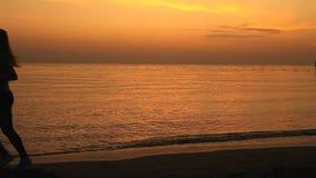 La ragazza funziona all'alba lungo la spiaggia video d archivio
