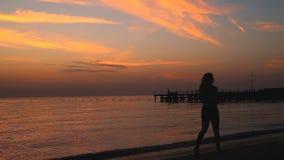 La ragazza funziona all'alba lungo la spiaggia stock footage