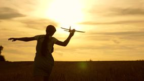 La ragazza funziona con un aereo del giocattolo sul campo nei raggi di slint i bambini giocano l'aeroplano del giocattolo sogni d stock footage