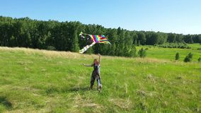 La ragazza funziona con un aquilone su un campo verde Risata e gioia, umore festivo Vacanza estiva stock footage