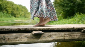 La ragazza funziona lungo il ponte del piede sopra il fiume stock footage