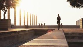 La ragazza funziona sulla strada in buon tempo Tempo soleggiato per addestramento campestre La ragazza funziona un giorno soleggi