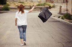 La ragazza getta la valigia che cammina giù la via Immagini Stock