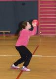 La ragazza getta una palla rossa nel canestro Immagine Stock